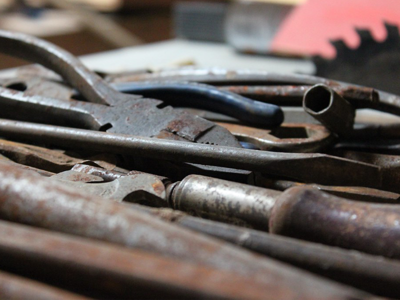 A selection of rusted tools on a bench