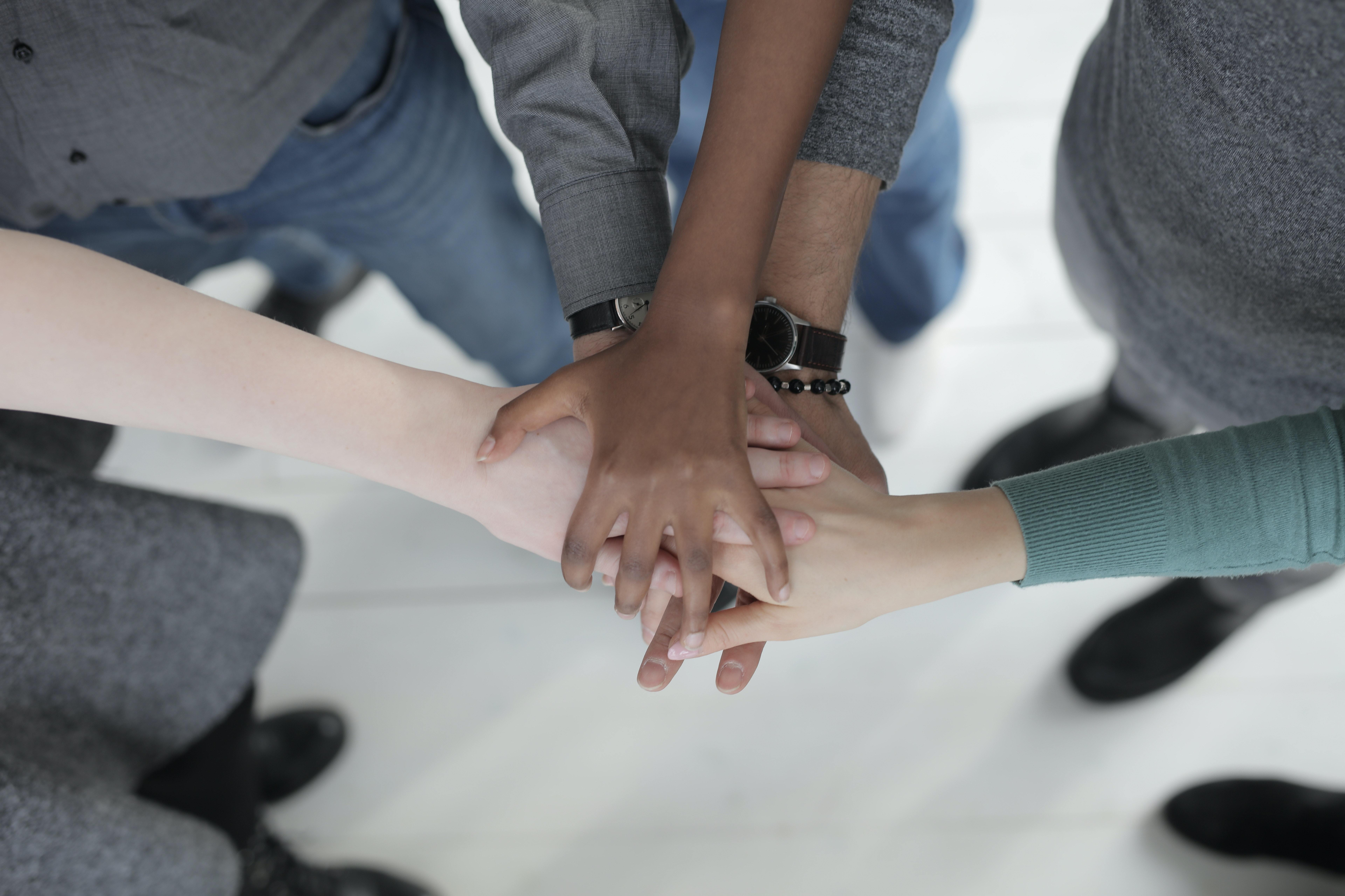 hands from people of different ethnicities reaching together