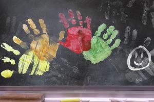 School blackboard with colourful handprints