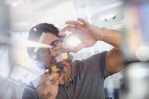 Focused, innovative male entrepreneur examining prototype