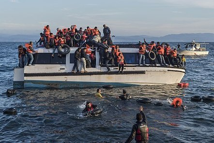 Refugees crossing the sea in a boat. Many are in the water.