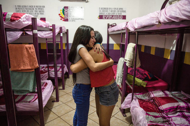 Two Central American girls hugs while standing in a dormitory with four sets of bunks. they are wearing casual clothes, jeans and t-shirts. The bunk beds have pink sheets and towels draped on the ends.