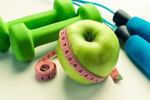 Green apple with hand weights, waist measure and skipping rope