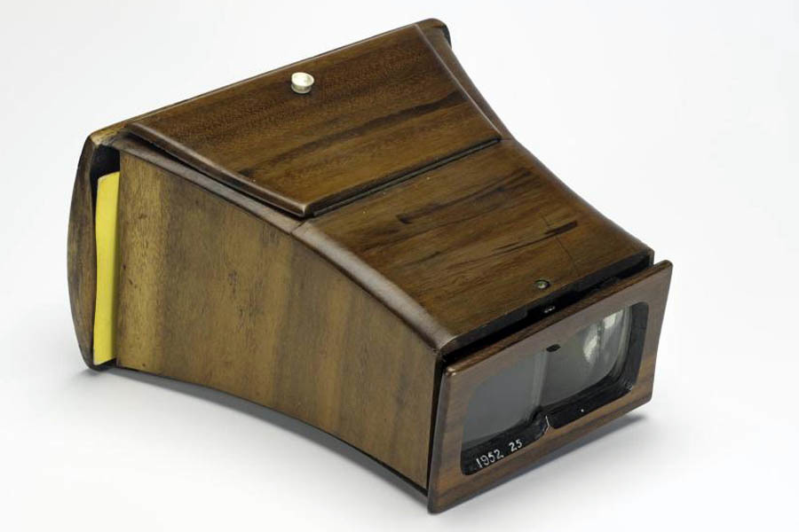 A lenticular stereoscope, wooden with eye holes clearly visible and edge of a stereo photograph visible to the left