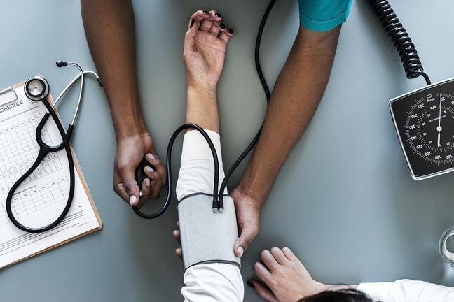 Doctor using blood pressure meter
