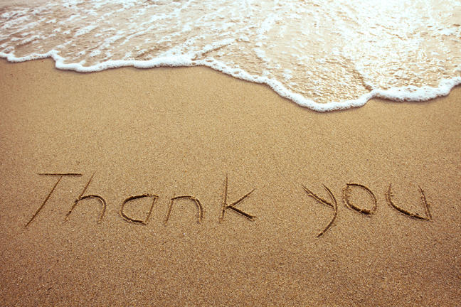 """Thank you"" written on the beach."