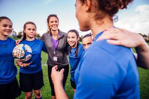 A team of young women football players with a coach