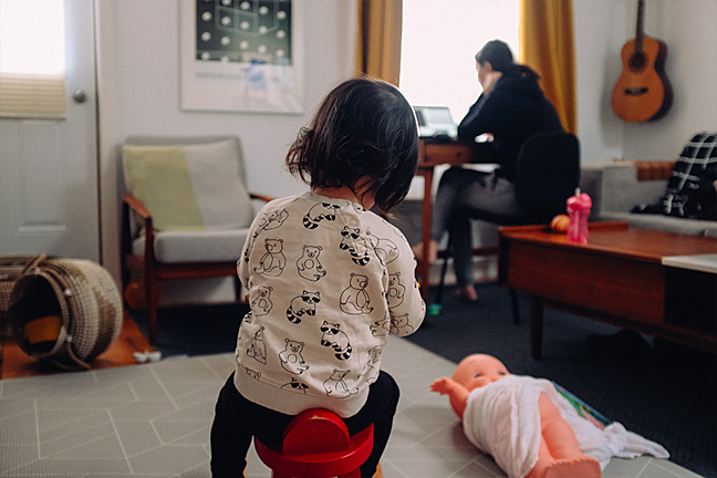 Young girl playing alone while mother is using laptop