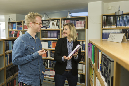 A lady recommends a book to man at a library