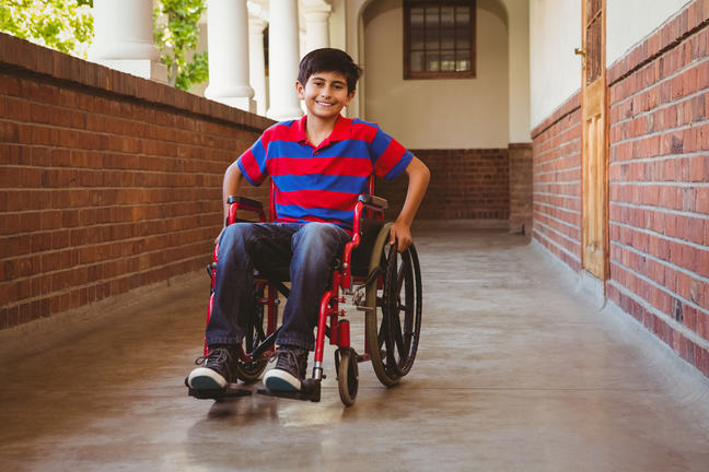 Boy sitting in wheelchair, smiling