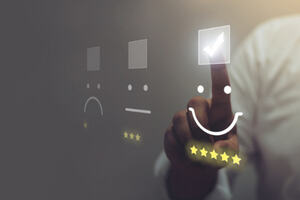 Figure clicking a smiley face review on a computer screen
