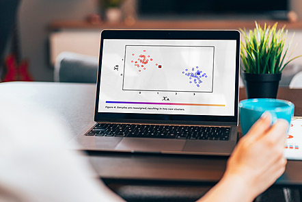 Laptop on a desk with its screen displaying a graph.