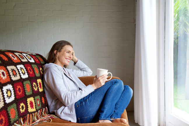 Smiling older woman relaxing at home with cup of tea.