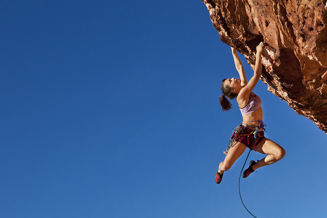 A woman dangling from a challenging rock face whilst rock climbing.