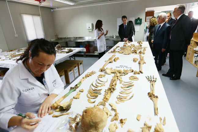 Forensic anthropologists from the Centre for Missing Persons in Cyprus examines a skeleton whilst visitors are being told about the work in the laboratory by another forensic anthropologist
