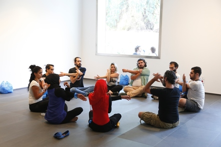 A group of adults sitting in a circle, doing stretching exercises
