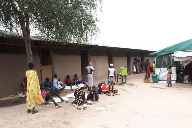 People waiting outside of a makeshift hospital tent next to a building in Lankien, South Sudan