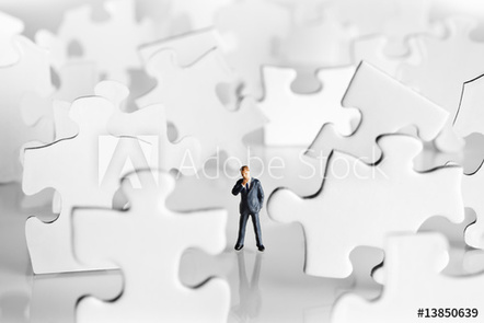 A man standing in a rain of puzzle pieces