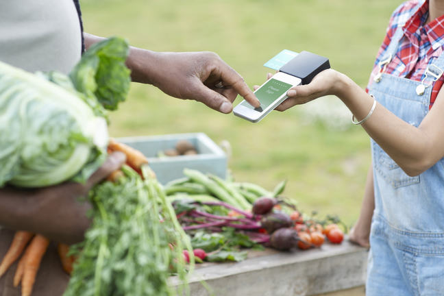 Man paying for vegetables with mobile add-on