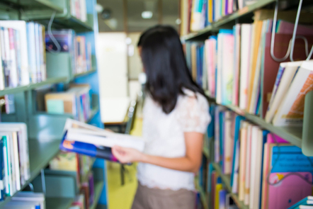 Young woman at library shelves