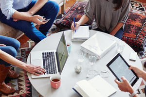 Group of people sitting around a coffee table using laptops and devices.