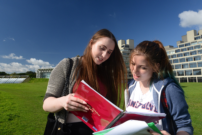 Students reading outside UEA building