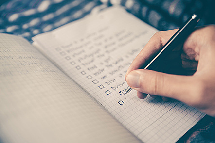Person writing items in a checklist © Glenn Carstens Peters, Unsplash