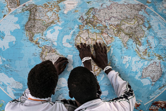 Two teenage boys from Gambia are looking at a map of the world. We see them from behind with their hands on the picture of Africa.