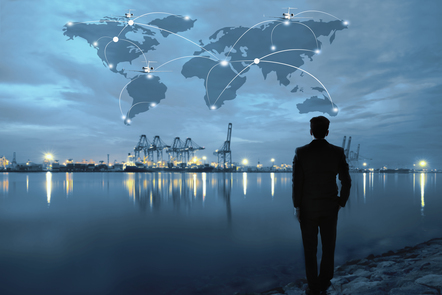 A man in a suit faces a shipping yard that stands before him across a body of water. The image has been graphically enhanced to show a connected world map in the sky above the shipyard.