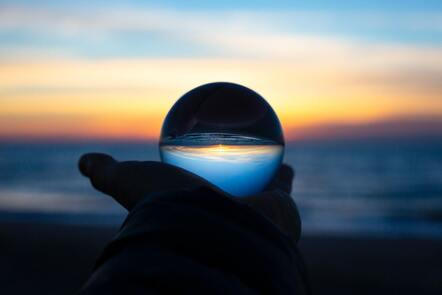 A person holding a clear glass sphere against a sunset horizon on a beach.