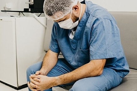 Stressed doctor, sitting in corridor