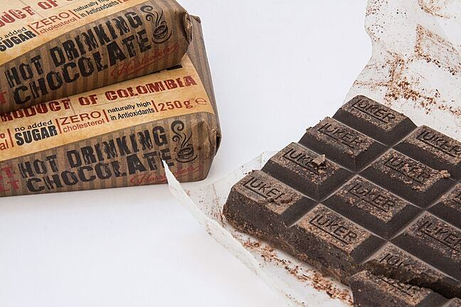 Three bars of hot drinking chocolate, one opened. On the packaging of the unopened are claims such as 'no added sugar', 'zero cholesterol', 'naturally high in antioxidants', and 'Produce of Columbia'