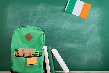 Learning languages concept - green backpack, flag of Ireland, books and notebooks on the background of the blackboard