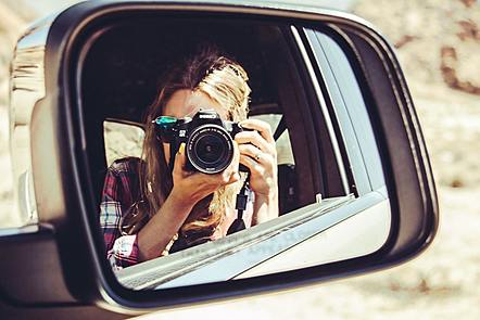 Woman taking photograph of herself in car side mirror.