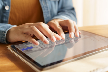 Hands typing on a tablet keyboard.