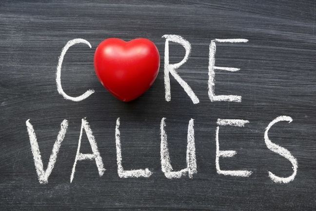 the words core values written on a chalk board with a red heart replacing the o in core