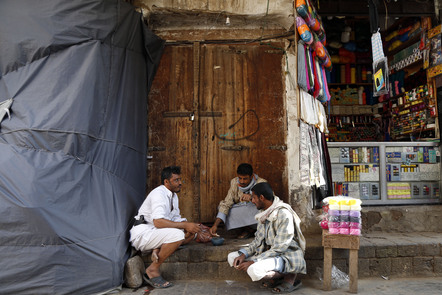 Yemeni shops' owners take their breakfast at a road at a market with historic buildings in the Old quarter of Sana'a.