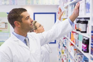 Two pharmacists reaching for medicines on a shelf.