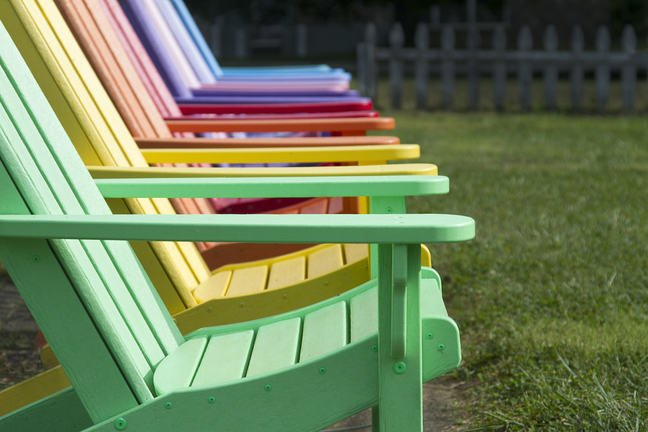 A row of colourful painted adirondack wooden chairs outdoors
