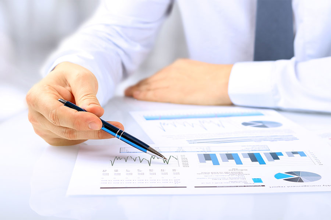 Businessperson evaluating data charts with a pen