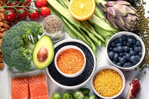 Selection of healthy food. Clean eating concept. Cooking ingredients with fish, superfood, vegetables, artichokes, brussel sprouts, fruits, legumes and blueberries.