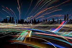 A darkened city skyline with many coloured lines crossing in all directions