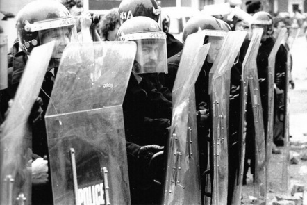 A line of police in riot gear stand behind large riot shields in 1981
