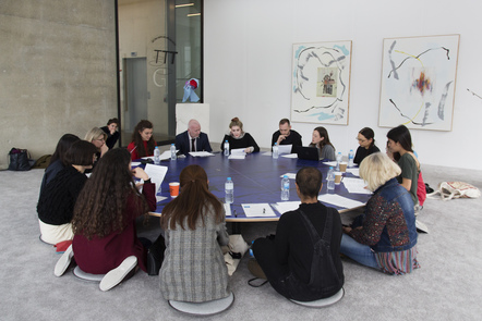 Decorative image, people sat on cushions at a large round table, reading documents on the table. Turn the Tide – Curating Contemporary Art graduate project, Show 2017