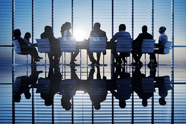 group of men and women in a meeting at work. stylised image with reflection in the polished floor.