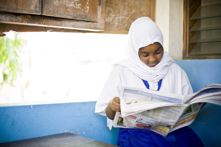 A young person reading a newspaper
