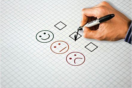 La imagen muestra un dibujo de tres caras: una sonriendo, la segunda neutral y la tercera con expresión de descontento. Al lado de cada cara hay un pequeño cuadrado y se observa una tilde dibujada en el cuadrado que está al costado de la segunda cara.