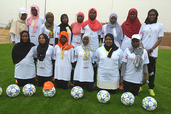 group of women wearing hijab with footballs in front of them training to be sport development coaches