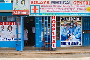 The entrance to a hospital called Solaya medical centre in Kenya. Building is blue with blue railings around and there is detail on the hospital signage about the services offered at the hospital which is a 24 hour 7 days a week hospital