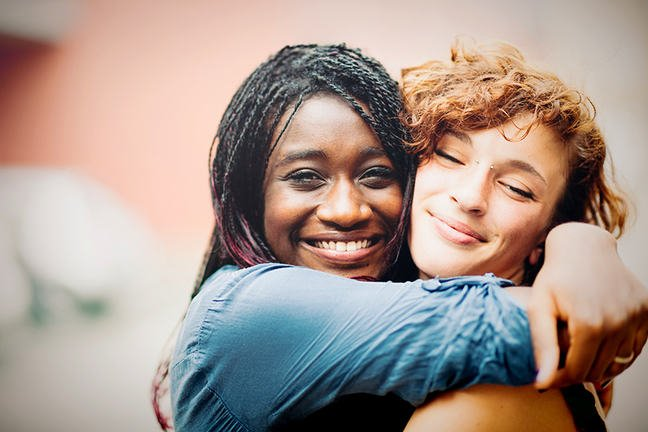 black female and white female hugging and smiling